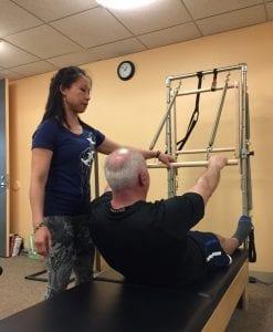 EMPS Pilates Teacher and Studio Owner Sarah de Guia with client on Half-Trapeze Tower